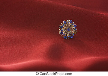 A shiny metal button on a background of red cloth
