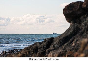 A ship on the horizon behind rocks.