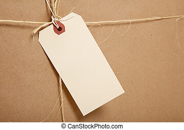 A Shipping Box Ties with string with a blank label - A brown...