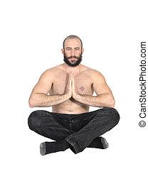 A shirtless man sitting doing yoga with a beard