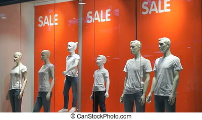 A shop window with mannequins indoors. Words SALE