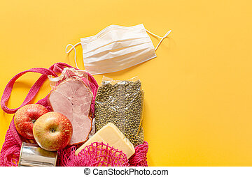 A shopping bag with basic food during quarantine and a protective mask.
