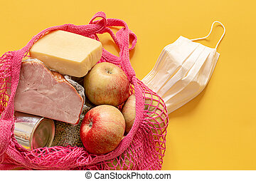 A shopping bag with basic food during quarantine and a protective mask nearby close up.