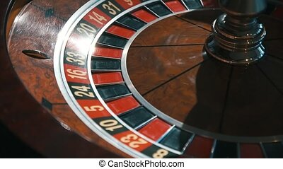 A shot of a casino roulette in motion, the ball stops at 27 red thirty six/Better luck next time