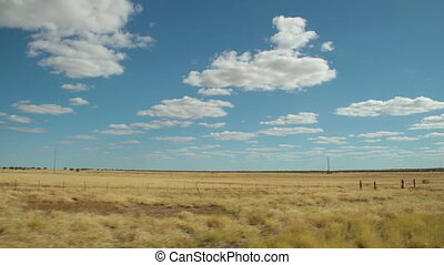 A shot of a land and sky - A wide shot of a yellowish land....