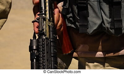 A shot of a loaded rifle - A close shot of a gun being held...
