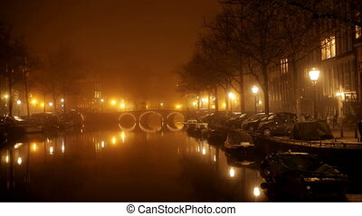 a shot of canal and street scene in amsterdam at night