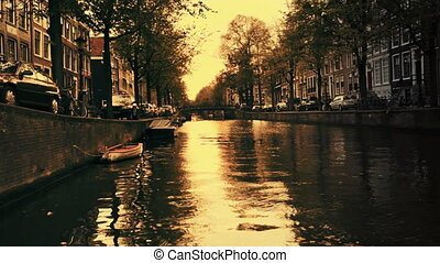 a shot of canal and street scene in amsterdam at sunset