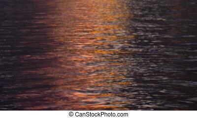 A shot of orange reflection of the ocean - A medium shot of...