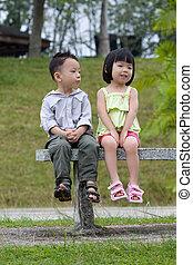 A shy little boy try to kiss a little girl