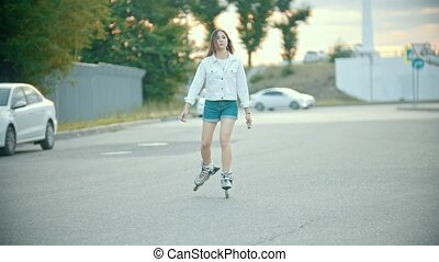 A shy teenage girl in rollerblades skating on the road. Mid...