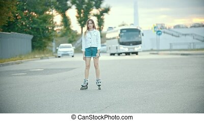 A shy teenage girl in rollerblades standing on the road. Mid...