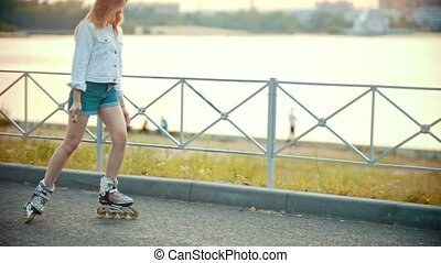 A shy teenage girl skating on the waterfront - early sunset....