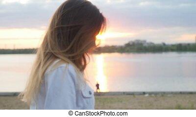 A shy teenage girl walking on the waterfront near the beach....