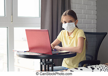 A sick girl sits at a table and is engaged in learning online, looked into the frame