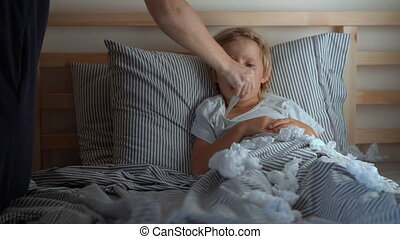 A sick little boy in a bed. Mother measures his temperature. Baby flu concept