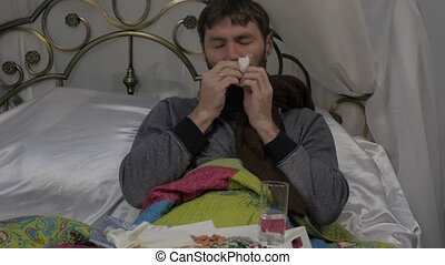 A sick man blowing his nose as having a runny nose during a...