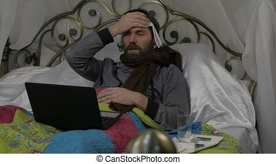 A sick man lies in a bed with a warm scarf around his neck and a towel on his head, video chatting with doctor on a laptop. slow motion