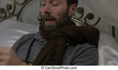 A sick man lies in a bed with a warm scarf around his neck,...