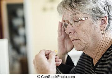 Sick senior woman taking her pills at home