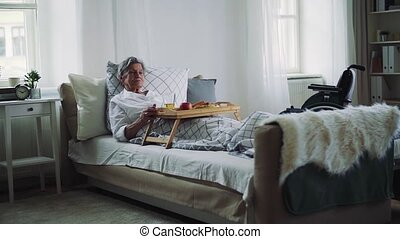 A sick senior woman with food on a wooden tray lying in bed...