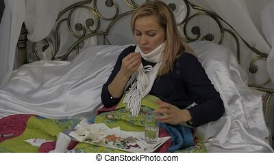 A sick woman lies in a bed blowing his nose as having a...