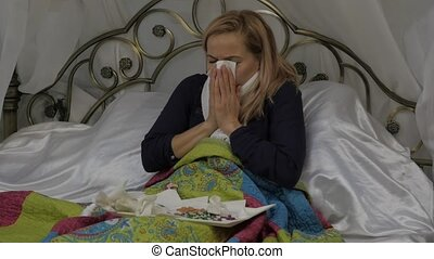A sick woman lies in a bed with a warm scarf around his...