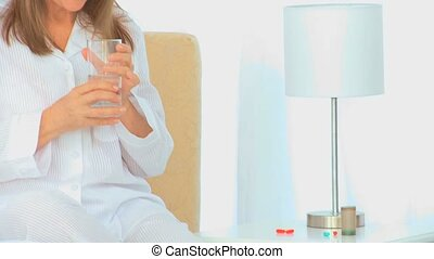 A sick woman with a glass of water in her bedroom