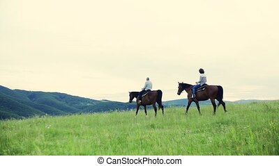 A side view of senior couple riding horses in nature. - A...