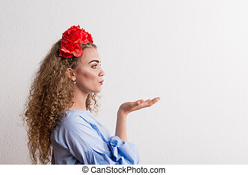 A side view of young beautiful woman with flower headband sending a kiss in studio.