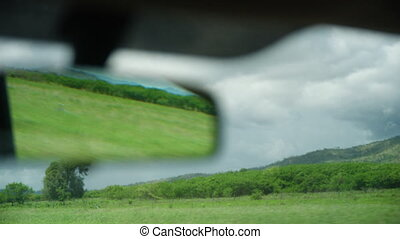 A sight from a car's rear mirror. - A shot focusing on a...