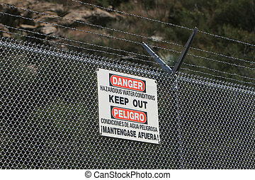 A sign warns of hazardous water conditions on a barbed wire...