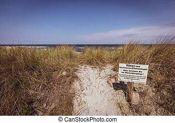 a sign with a warning sign stands at the dune of the Baltic Se