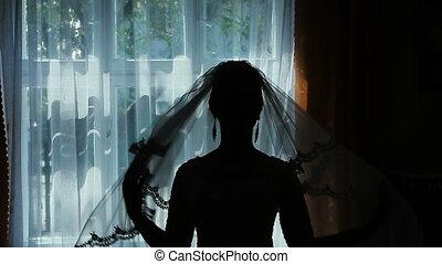A silhouette of a bride near the window.