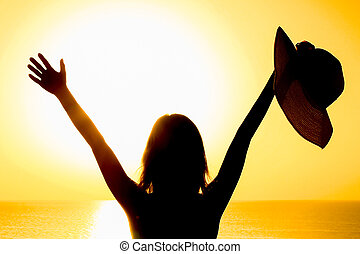 A Silhouette of a girl with a chair on a loggia balcony background. Happy woman with a hat in her arms while on vacation traveling.