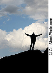 silhouette of a man in front of the blue sky