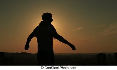 A silhouette of a man raise up hands on the roof at sunset background.