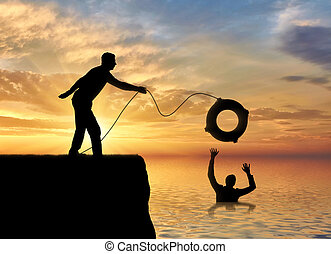 A silhouette of a man throws a lifeline to another man who...
