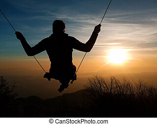 A silhouette of a person swinging towards the sun on the top of Mt. Lowe, Los Angeles, San Gabriel National Forest