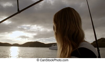 A silhouette of a woman on a boat at sunset