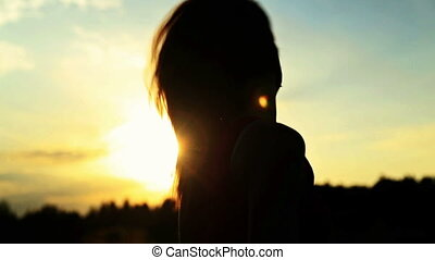 A silhouette of a woman  on a sunset turns her head