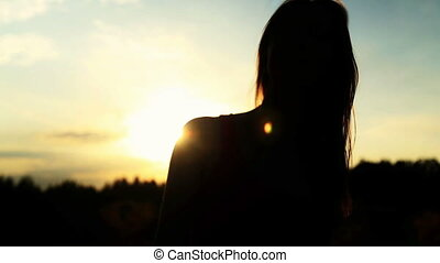 A silhouette of a woman  on a sunset turns her head and dancing