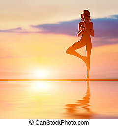 A silhouette of a woman standing in tree yoga position, meditating against sunset sky