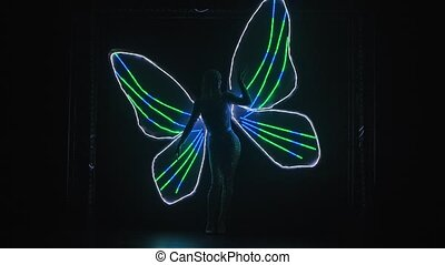 A silhouette of a woman with glowing butterfly wings can be seen on a black background. Theatrical vocal dance show. Slow motion.