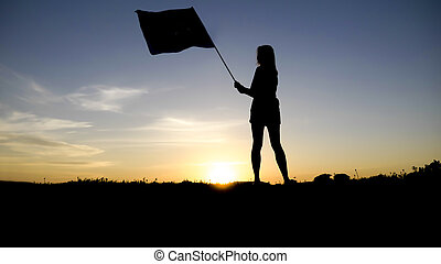 silhouette of people with flag on mountain top .