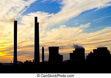 a silhouette of power plant at dusk