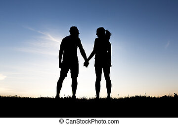 silhouette of romantic lovers with sunset on the back