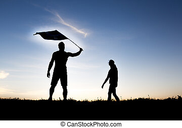 silhouette of two people at with sunset on the back with flag