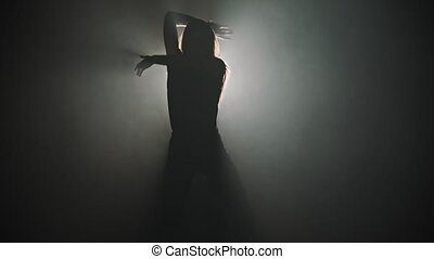 A silhouette of young attractive woman dancing with her hands on the background of bright lighting