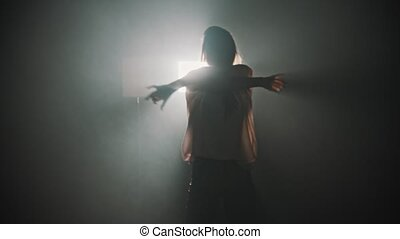 A silhouette of young woman dancing with her hands on the background of bright lighting